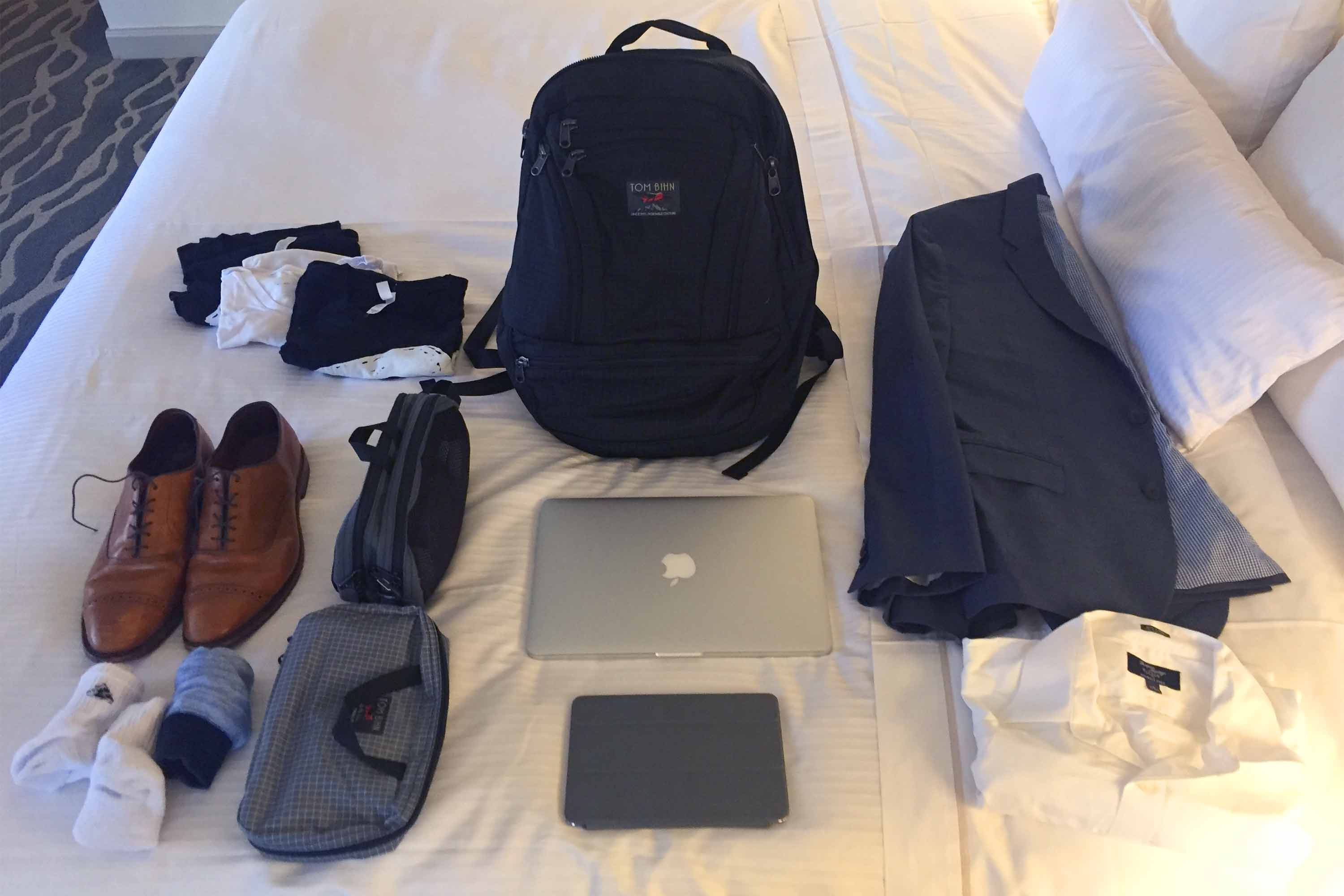 A backpack surrounded by the items that were packed inside it, including a suit jacket, a dress shirt, a laptop, an iPad, and some other clothing