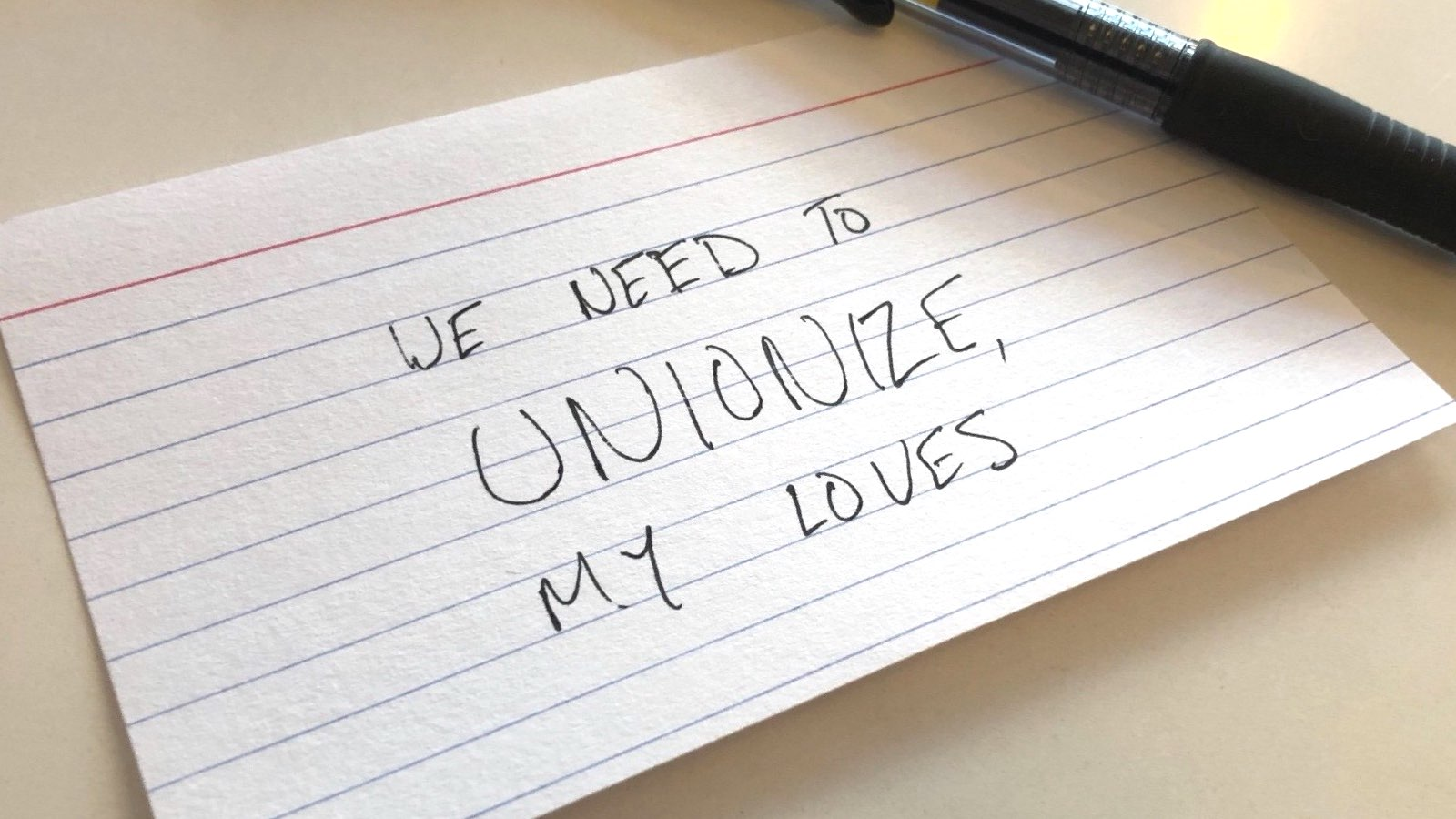 "The phrase ""We need to unionize, my loves"" hand-written on an index card in black ink."
