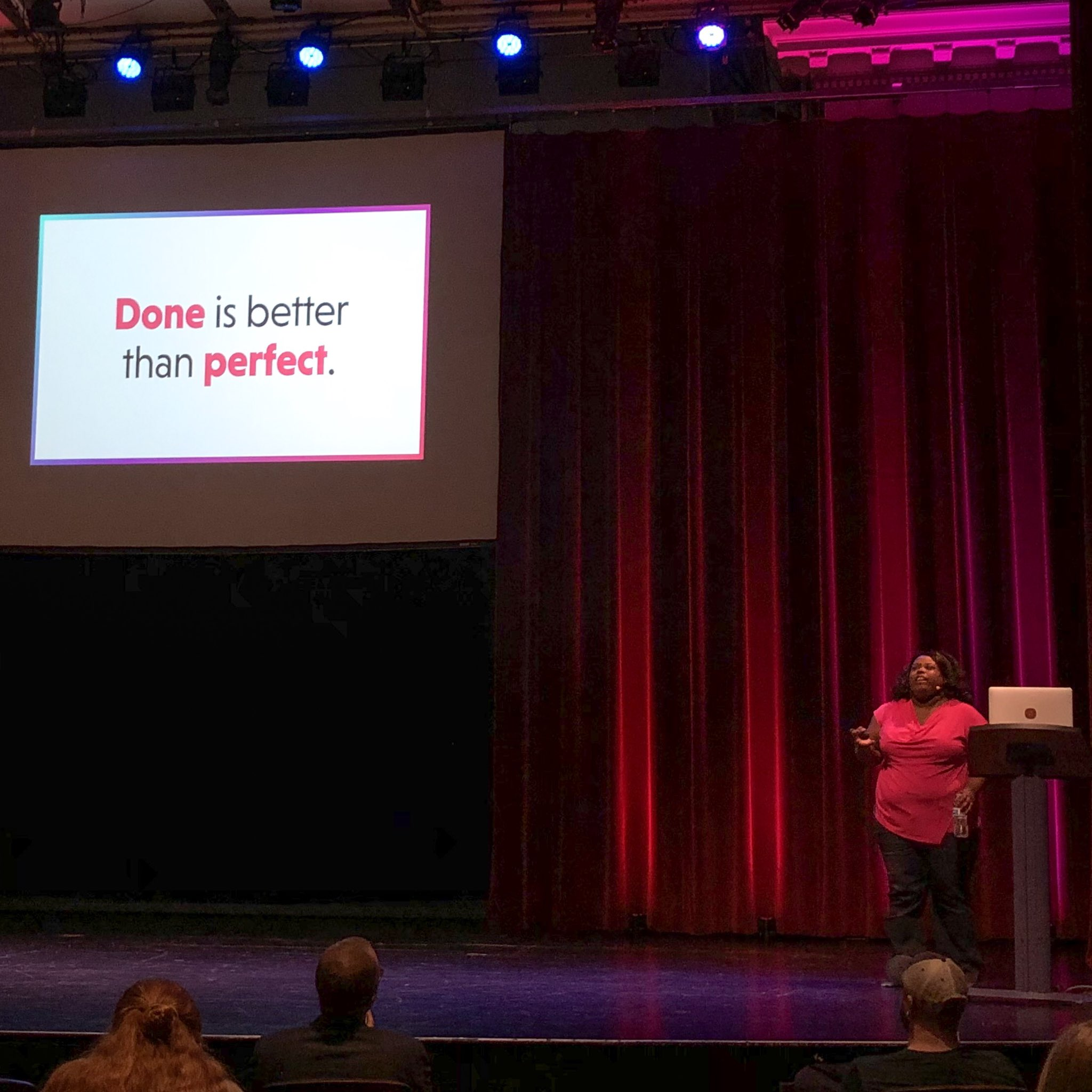 "Mina Markham on stage, standing in front of a slide that reads ""Done is better than perfect"""