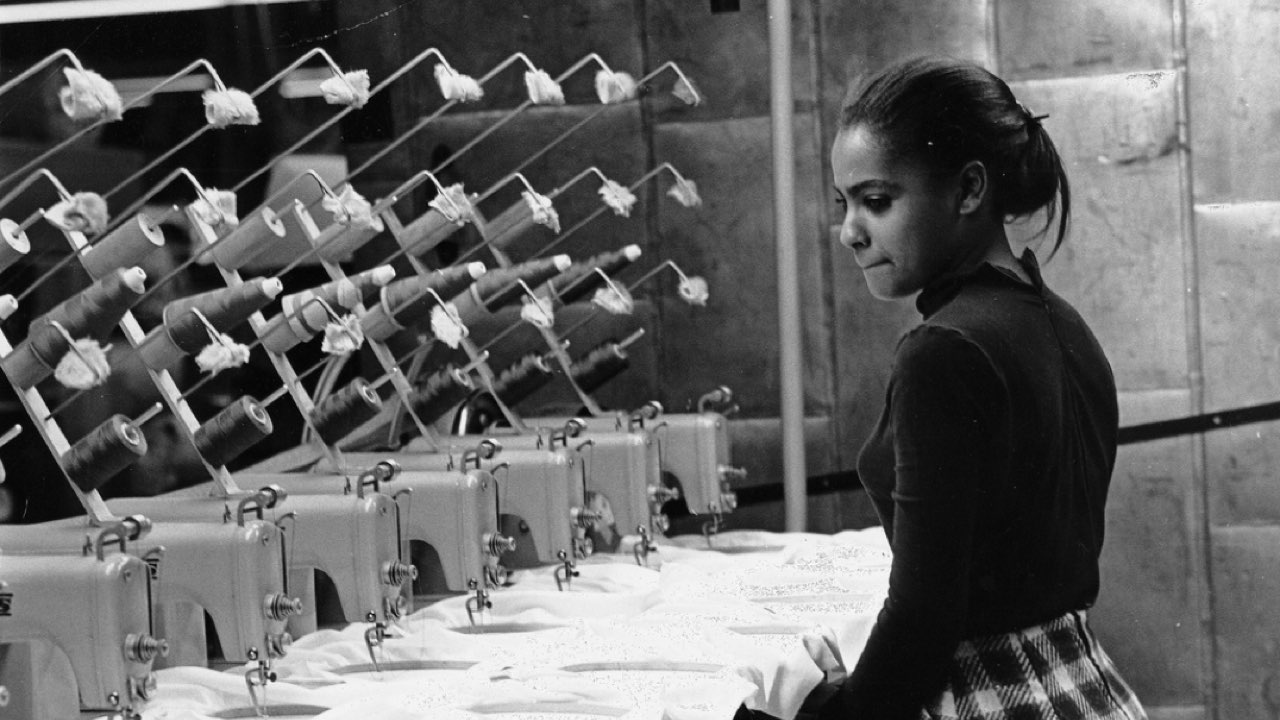 A young Black woman stands in front of seven electric sewing machines, watching them as they manufacture clothing automatically.
