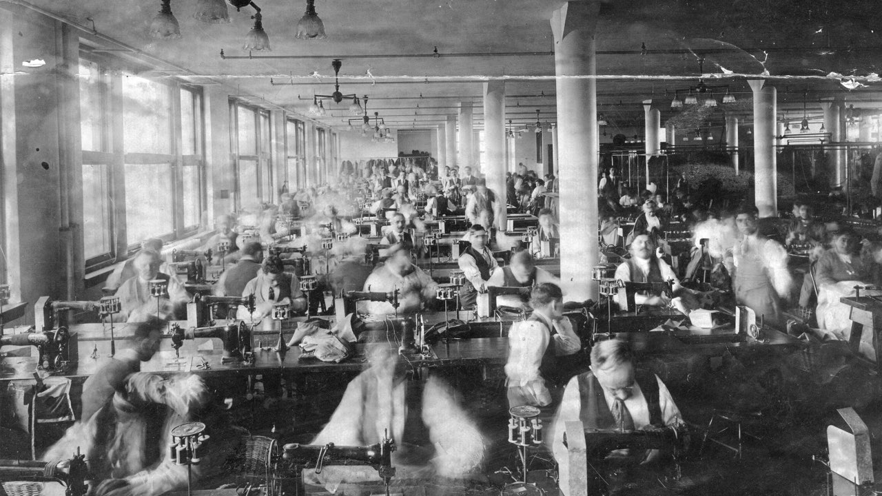 A factory room full of male employees, who are seated while working sewing machines. There is a male supervisor standing near the right.