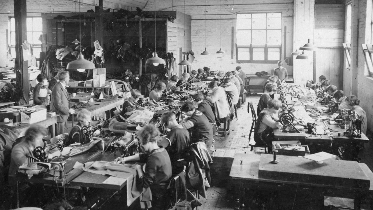 A factory room full of female employees seated working sewing machines. There is a male supervisor standing near the left.