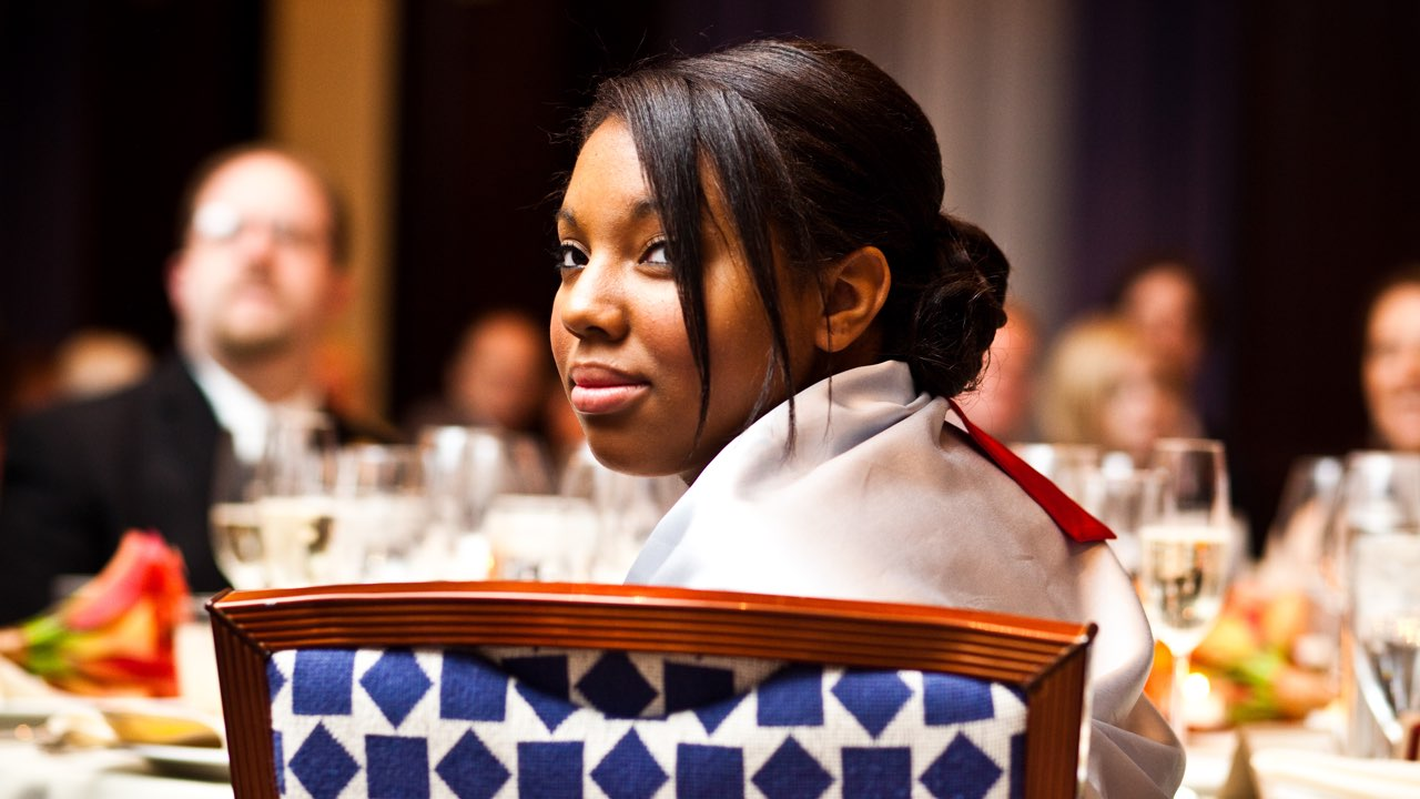 A Black woman sits at a fancy dinner table, looking over the back of her chair toward the camera. She has a slight smile on her face. Behind her, wine glasses and other dinner guests can be seen in soft focus.