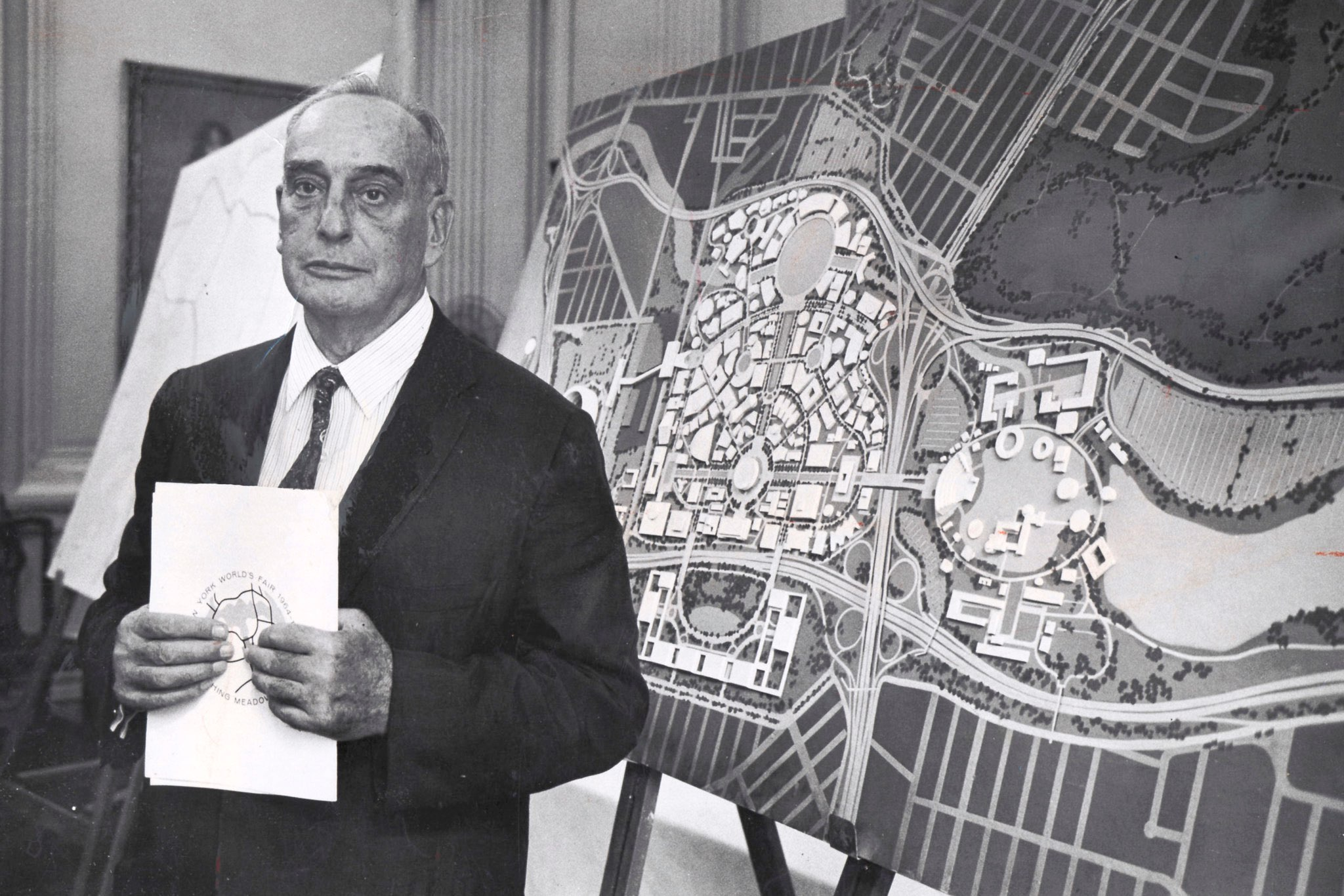 Robert Moses wears a dark suit and tie while holding a folder containing his plans for the New York World's Fair. Moses stands in front of a map of the park where the World's Fair will be held.